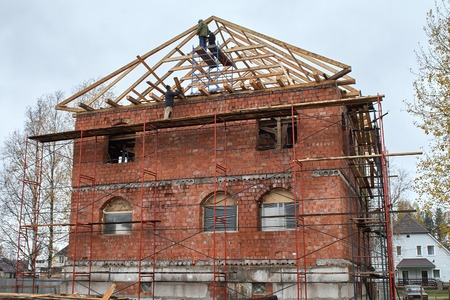 Workers are installing rafters on the roof of a brick house, standing on scaffolding.