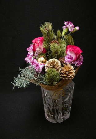 Christmas bouquet with red roses, bush carnations, pine cones, cypress branches, pink pepper and yellow balls. New Year composition on a dark background.