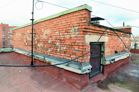 A view of the elements of the roof of a modern multi-storey brick building. Ventilation, the door to the attic, the tower elevator shaft. Wires, cables, waterproofing and drainage. St. Petersburg Stock Photo