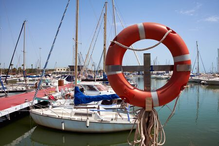 Lifebuoy in the marina for yachts. Red circle in the seaport of Marina de las Dunas, Guardamar del Segura, Alicante, Spain. Stock Photo