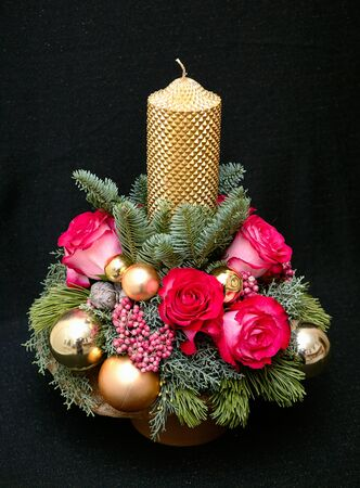 Christmas composition with a candle in the center, pine branches, juniper, pink roses, pink pepper, cones, and golden balls. New Year composition on a dark background.