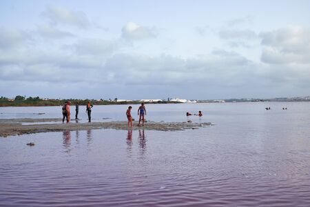 curative: Torrevieja, Spain - June 26, 2016: Different people, men, women and children are taking procedures on a salt lake with pink water. At lake Las Salinas. Editorial