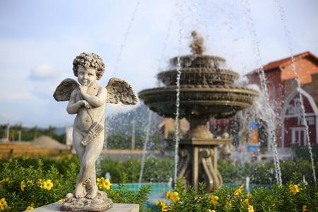 baby angel: scultura Baby Angel con una fontana Archivio Fotografico