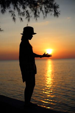 mujer mirando el horizonte: mujer de pie en la playa, la celebraci�n de sol en las manos