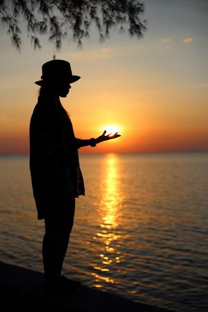 mujer mirando el horizonte: woman standing on beach, holding sun in hands Foto de archivo