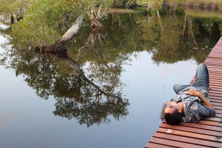 Man lying on wooden bridge