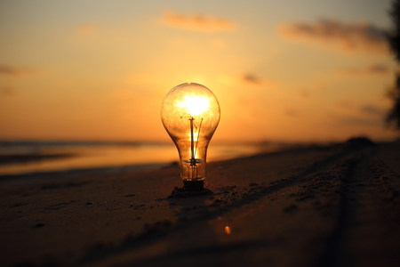 electric light bulb and sun at beach sunset sky Stock Photo