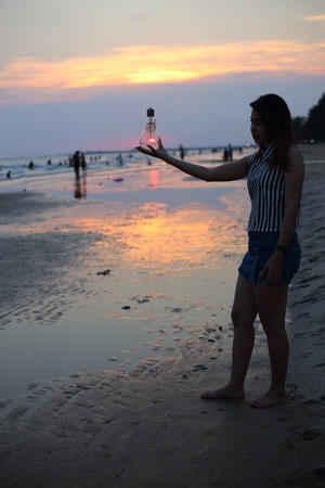 Woman holds the electric light bulb and the sun on the beach at sunset