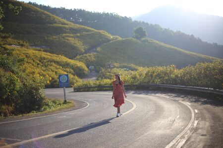 Women are strolling and Mountain scenery filled with yellow flowers or Mexican sunflower (Tung Bua Tong) at Doi Mae U Kho, Mae Hong Son, Thailand. Banco de Imagens