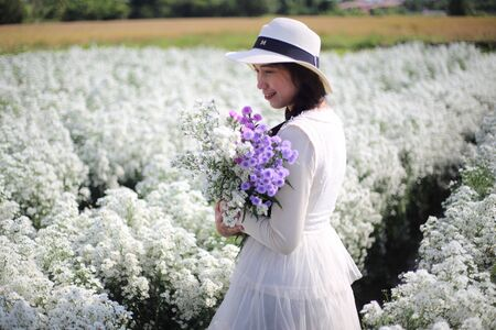 Woman holding flowers in Cutter flower fields at Mae Rim district, Chiang Mai, Thailand.