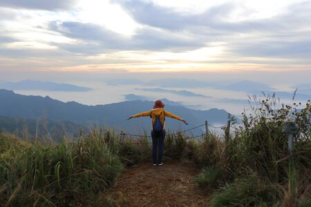 A woman standing in the fog and mountain view at Phu Chi Fa National Park, Chiang Rai, Thailand