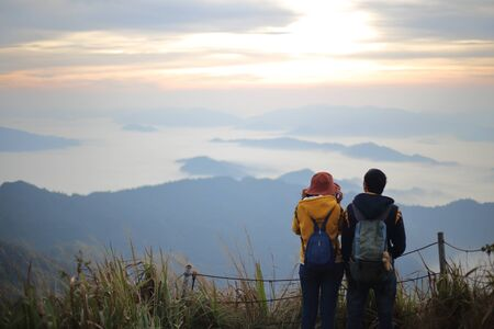Man and woman standing in the fog and mountain view at Phu Chi Fa National Park, Chiang Rai, Thailand
