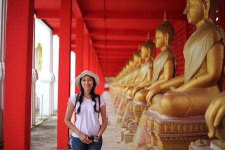 Woman standing at the line of Buddha statue in Wat Tha Sung, Uthai Thani, Thailand.