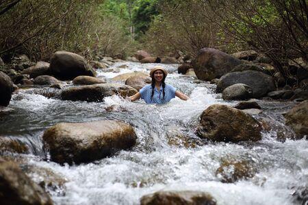 Woman soaking in the Trok Nong waterfall in Chanthaburi, Thailand