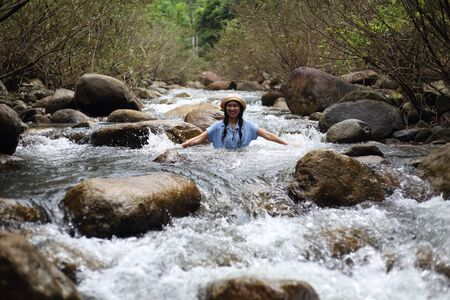 Woman soaking in the Trok Nong waterfall in Chanthaburi, Thailand Stockfoto