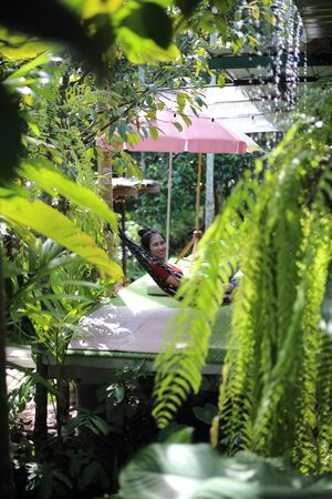 Woman sitting in garden with green plants