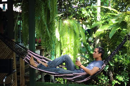 Man sitting in garden with green plants Stock Photo
