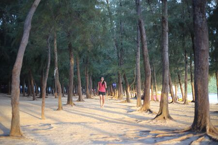 A woman standing on a pine forest by the beach