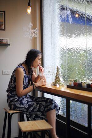 Woman drinking iced coffee using straws