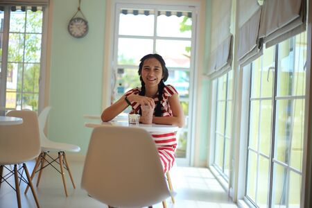 A woman sitting and drinking coffee in a cafe Stock Photo