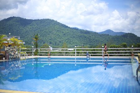 Woman standing at the pool area with mountain views Stock Photo