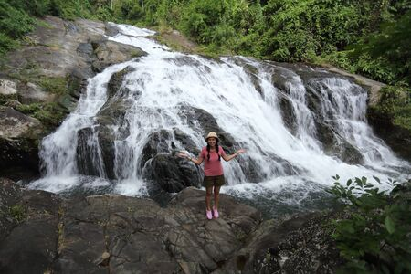 Woman standing on the rocks at Khao Soi Dao waterfall in Chanthaburi, Thailand Stock Photo