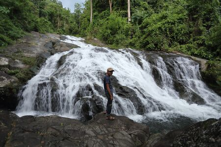 Man standing on the rocks at Khao Soi Dao waterfall in Chanthaburi, Thailand Stock Photo