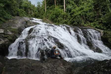 Man sitting on the rocks at Khao Soi Dao waterfall in Chanthaburi, Thailand