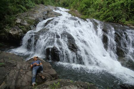 man lying on the rocks at Khao Soi Dao waterfall in Chanthaburi, Thailand