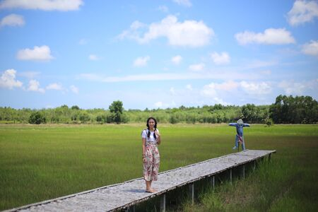 A woman standing on a wooden bridge in a rice field