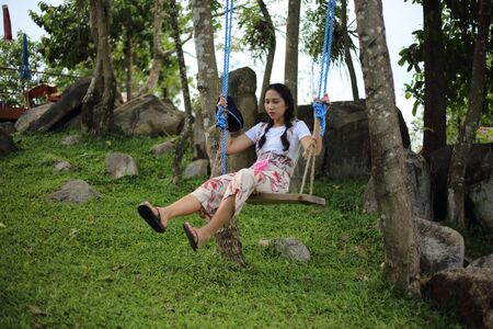A woman sitting on a swing in the garden Stock Photo