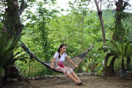 Woman sitting in a hammock in the garden