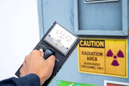Der Vorgesetzte verwendet das Vermessungsmessgerät, um das Strahlungsniveau in der radioaktiven Zone zu überprüfen