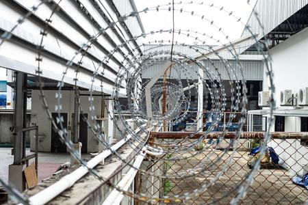 Recinzioni di filo spinato installate sul muro per proteggere l'area dai ladri o impedire la fuga dei prigionieri.