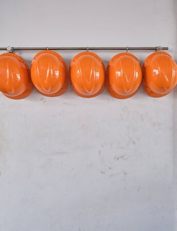 Hard hats hanging on hook against the dirty white wall.