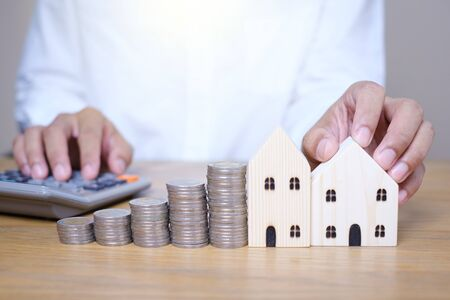 Hand putting coins stacks near wooden house model and use calculator to calculate on the wooden table. Saving money for future investments and Planning to save money to buy a house. Archivio Fotografico