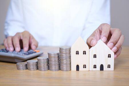 Legen Sie Münzenstapel in der Nähe des Holzhausmodells von Hand und verwenden Sie den Taschenrechner, um auf dem Holztisch zu berechnen. Sparen Sie Geld für zukünftige Investitionen und planen Sie, Geld zu sparen, um ein Haus zu kaufen. Standard-Bild