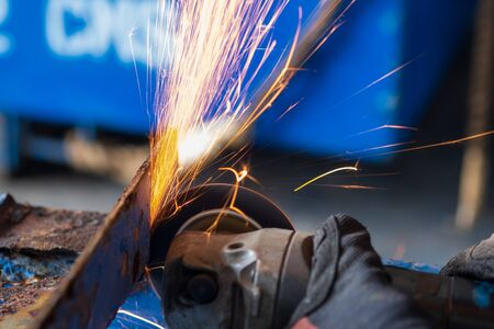 worker cutting steel with grinding machine and splashes of sparks in workshop.