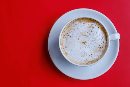 The top view of the cappuccino coffee in a white cup with milk froth on a red table