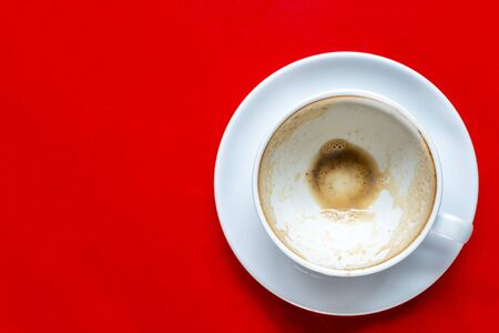 The top view of the empty coffee in a white cup with milk froth on a red table