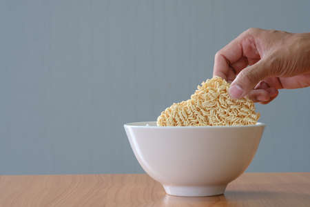 uncooked Instant noodles and black bowl on wooden table and gray background This diet is suitable for the spread of COVID. -19 and in situations saving money is required