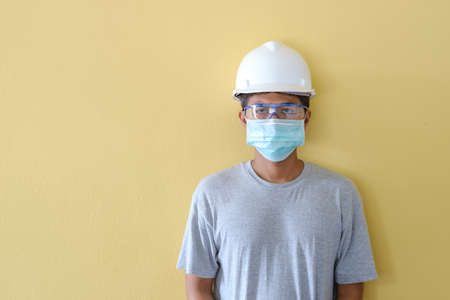 Workers wearing helmets and masks for safety in the face of the epidemic stand in front of a yellow scene.