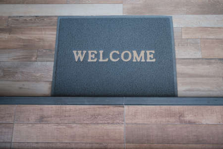 A doormat with the word Welcome rests on the floor to welcome people entering.