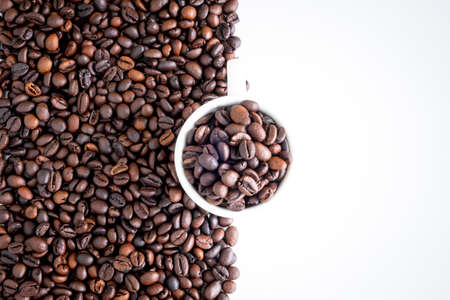 Dark roast coffee beans and the white cup background, top view
