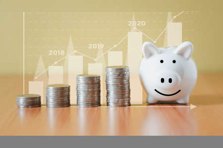 Stacking coins pile and white piggy bank for savings with money and planning step up to growing, Saving money for retirement fund and the future plan concept.