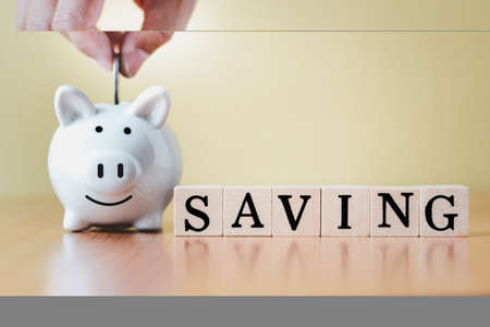 Stacking coins pile and white piggy bank for savings with money and planning step up to growing with business graph background, Saving money for retirement fund and the future plan concept.