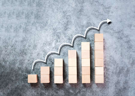Wooden block stacking as ladder, step stairs with white arrow up on gray background, Concept of success in business growth, copy space