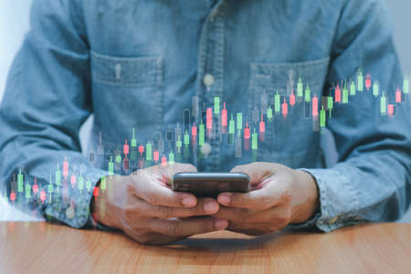 Concept digital money and stock business, Business men use smartphone with bar graph of stock and stock table