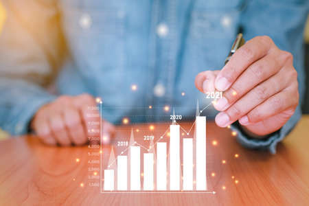 Businessman use the smartphone to plans business growth in 2021. Concepts of finance, marketing, Sales increase and Business Growth Planning with technology. Analysis using graphs