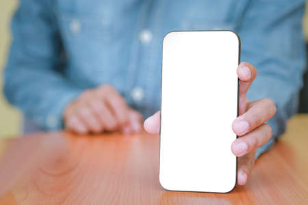 The man is handing out a white mobile phone screen to the front. Text can be placed in copy spaces. Concept of technology, Social and communication